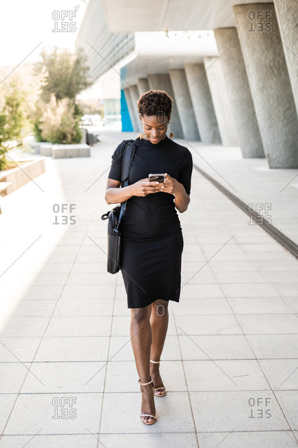 Focused stylish African American woman in black dress messaging smartphone while walking on street