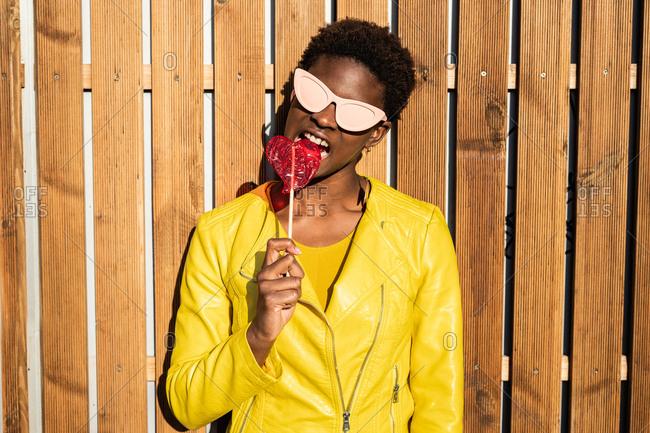 Trendy African American woman in sunglasses in yellow jacket enjoying heart shaped lollipop by wooden fence