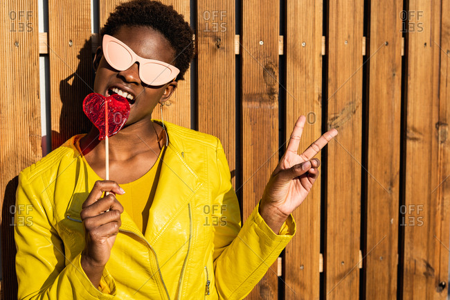 Trendy African American woman in sunglasses in yellow jacket enjoying heart shaped lollipop by wooden fence and gesturing peace sign