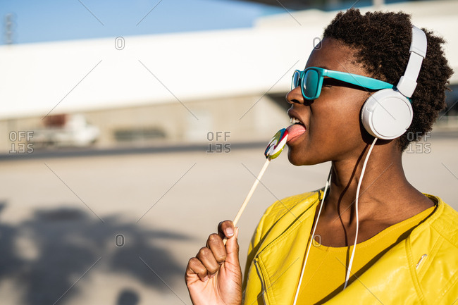 African American woman in sunglasses in yellow jacket enjoying a lollipop and listen to music on headphones