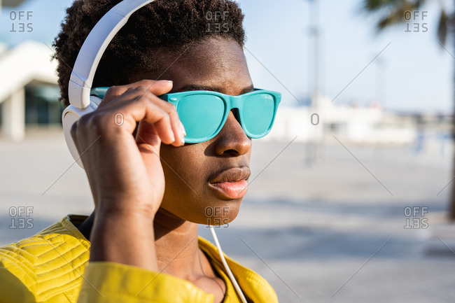 African American woman in stylish bright jacket and bright blue sunglasses using headphones standing near a modern building