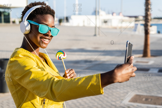 African American woman in sunglasses in yellow jacket enjoying a lollipop and listen to music on headphones while taking a selfie on a mobile phone