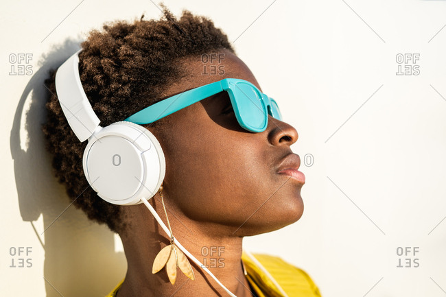 African American woman in stylish bright jacket and bright blue sunglasses using headphones leaning in a white wall