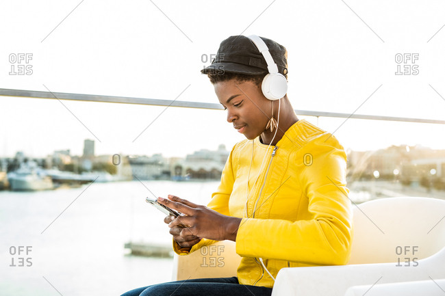 Side view of African American woman in stylish bright jacket using mobile phone and listen to music on headphones