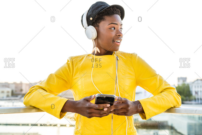African American woman in stylish bright jacket using mobile phone and listen to music on headphones