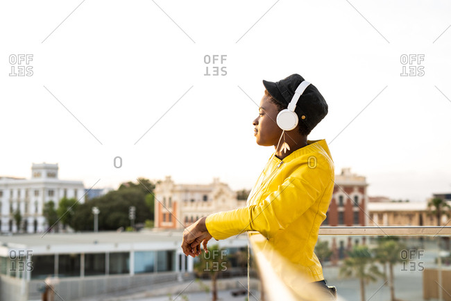 Side view content African American woman in trendy jacket listening to music in headphones while leaning on glass balcony and looking away on blurred background