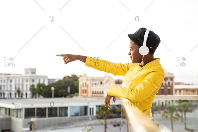 Side view content African American woman in trendy jacket listening to music in headphones while leaning on glass balcony and looking away pointing with finger on blurred background