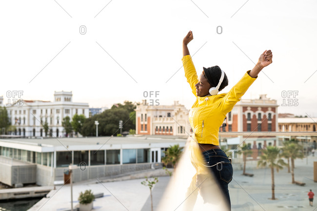Side view content African American woman in trendy jacket listening to music in headphones while leaning on glass balcony and looking away with arms up on blurred background