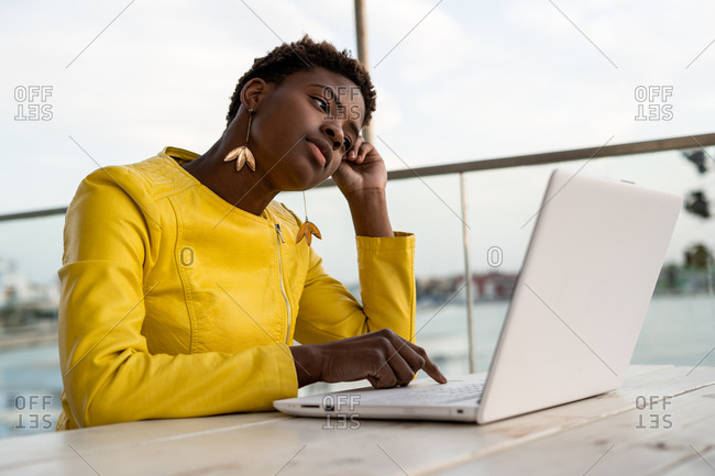 Tired African American woman in yellow jacket yawning while using laptop at wooden desk in city on blurred background
