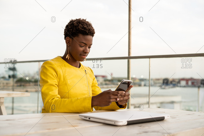 Concentrated African American female messaging smartphone while relaxing at wooden table