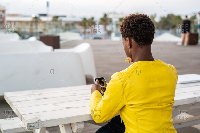 Back view of concentrated African American female messaging smartphone while relaxing at wooden table
