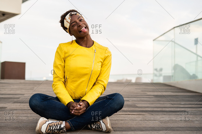 Stylish African American female in modern jacket relaxing sitting on wooden floor and looking at camera making silly faces