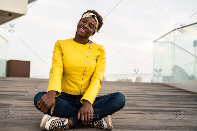 Stylish African American female in modern jacket relaxing sitting on wooden floor and looking at camera