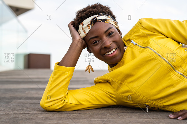 Stylish African American female in modern jacket relaxing lying down on wooden floor and looking at camera
