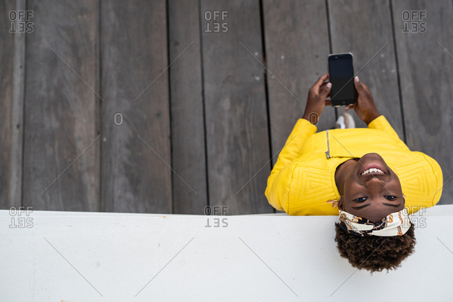 Top view of modern African American woman leaning on wall of modern building while using mobile phone