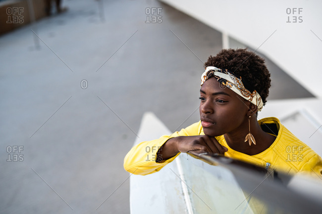 High angle of glad African American woman in stylish wear chilling on stairs leaning on the handrail and looking away
