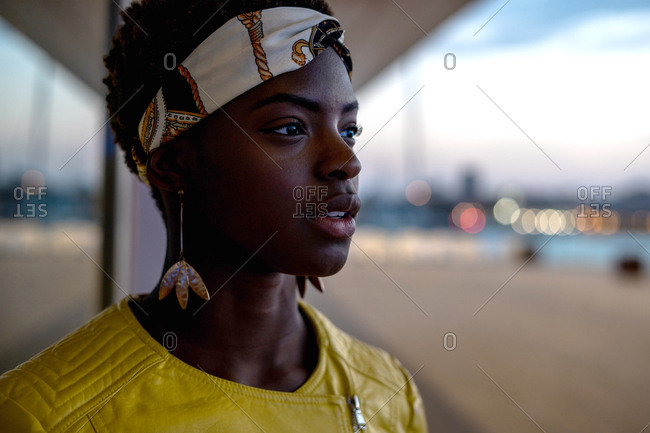 Side view of serene African American woman chilling on glass balcony and looking away on a evening