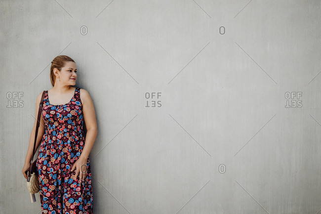 Smiling woman in summer colorful dress with flower looking away leaning on grey wall