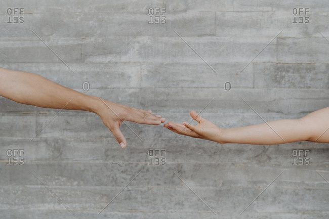 Tanned strong hands of crop man and woman touching on background of grey wall