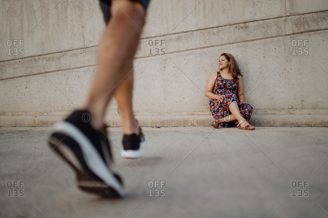 woman sitting on grey wall while crop man is walking to her