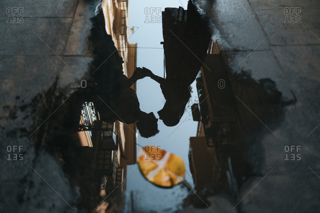 From above dark silhouette of romantic kissing couple reflecting in big puddle with autumn leaf in city road