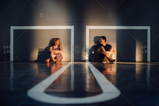 Charming couple sitting on floor of marked playground in sunlight and looking with tender