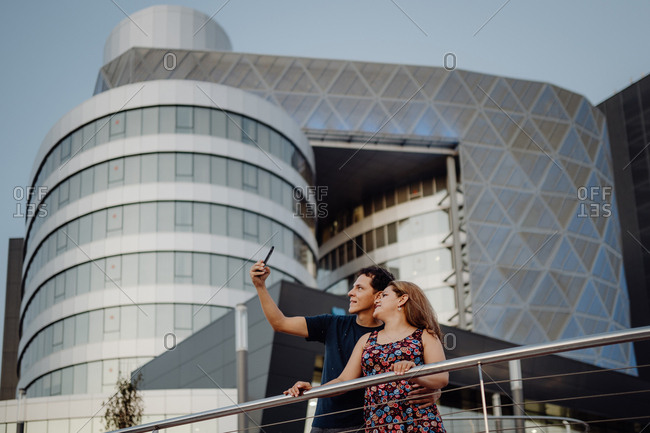 Romantic traveling couple taking selfie on mobile phone on background of amazing geometric building in balcony