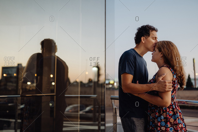 Side view of romantic couple bonding on road along urban building in sunlight