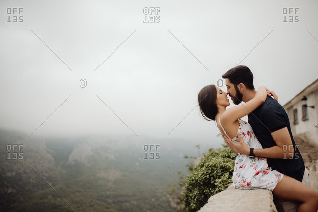 Casual tender couple hugging and kissing while standing at scenic viewing point against hazy mountain valley