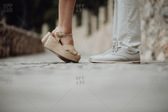 Crop side view of woman in sandals standing on tiptoe in front of casual man on pebbled pavement