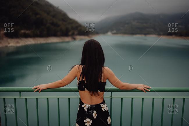 From behind slim brunette in open back dress leaning on handrail of bridge across still lake at scenic mountain valley