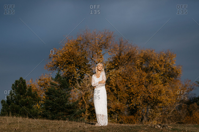 Beautiful blonde woman gazing at autumn countryside