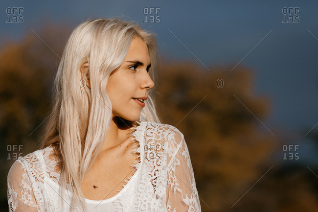 Tender woman with white blonde hair contemplating while standing at rural area with orange foliage