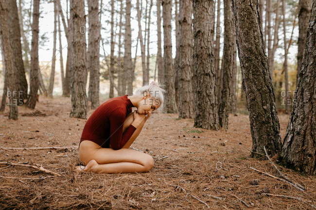 Beautiful modern woman resting barefoot in evergreen forest