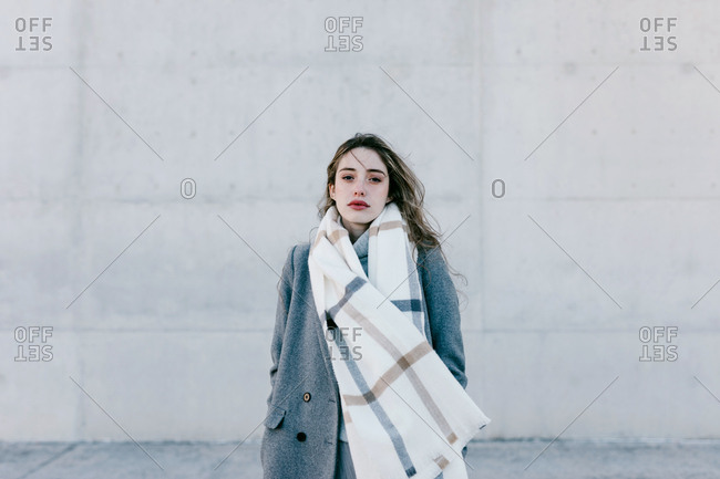 Young female looking at camera and in stylish gray coat and warm scarf standing against concrete building wall on city street on windy day