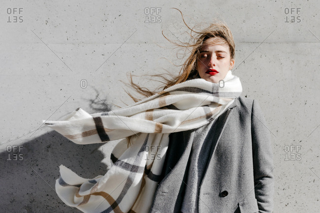 Young female with closed eyes and in stylish gray coat and warm scarf standing against building wall on city street on windy day