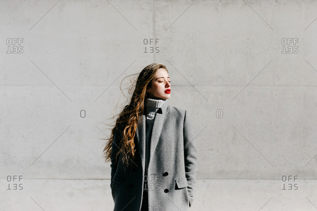 Young female with closed eyes and in stylish gray warm coat standing against building wall on city street on windy day