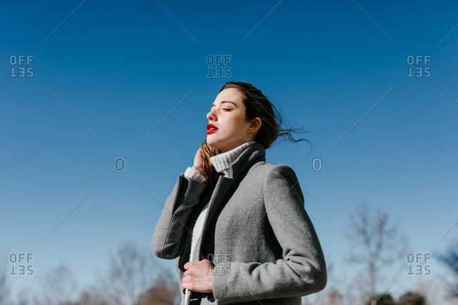 Side view of young female with closed eyes and in stylish gray warm coat standing against clear blue sky on windy day