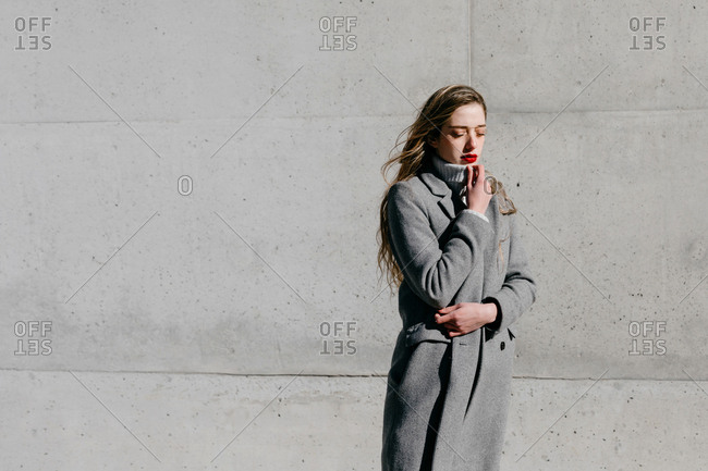 Side view of young female with closed eyes and in stylish gray warm coat standing against building wall on city street on windy day