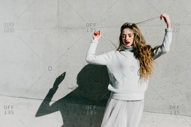 Young female model in stylish warm sweater and skirt closing eyes and touching long hair while standing against gray wall on city street
