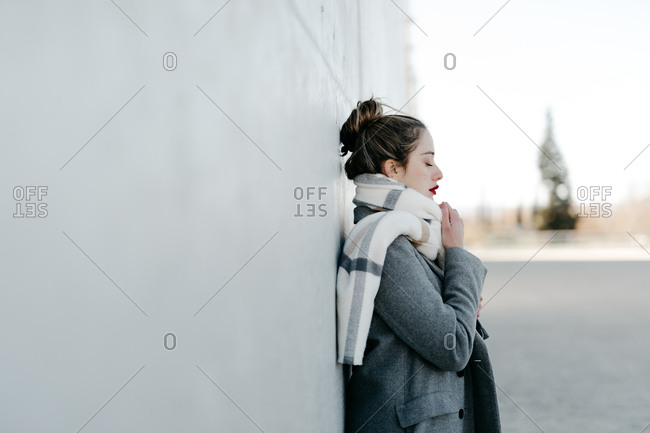 Side view of female with closed eyes and in stylish gray coat and warm scarf leaning against building wall on city street on windy day