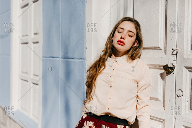 Young lady in elegant blouse with closed eyes in a sunny day while standing near white door of blue building on street