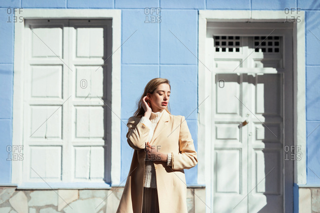 Young lady in elegant blouse with closed eyes while standing near white door and windows of blue building on street