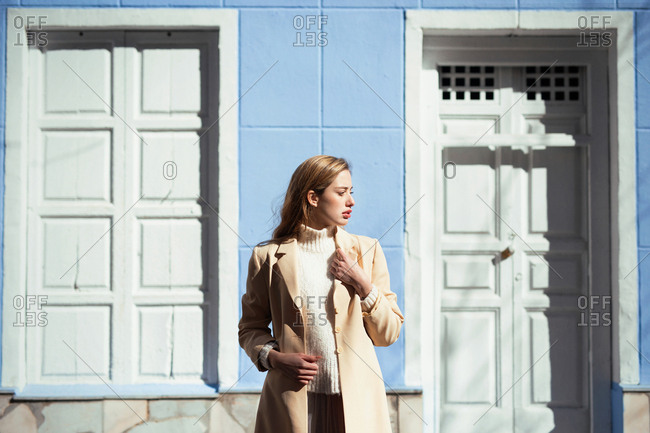 Young lady in elegant blouse looking away while standing near white door of blue building on street
