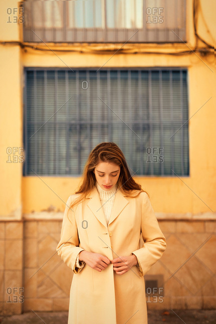 Sensual young female with long hair buttoning stylish coat and looking down while standing outside building on city street