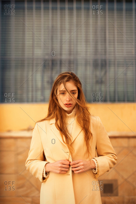 Sensual young female with long hair buttoning stylish coat and looking at camera while standing outside building on city street