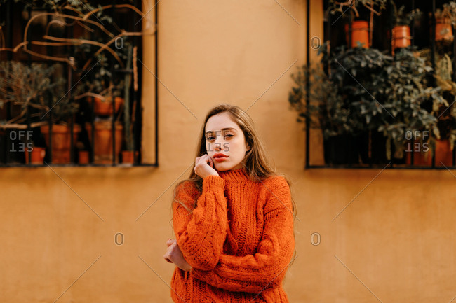 Sensual young female in trendy knitted sweater touching chin and looking at camera while standing outside house with potted plants on windows