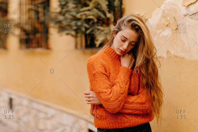 Sensual young female in trendy knitted sweater touching chin with closed eyes while standing outside house with potted plants on windows