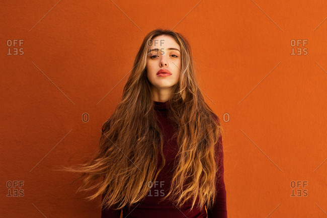 Portrait of attractive young woman with long hair while standing against orange wall on street looking at camera