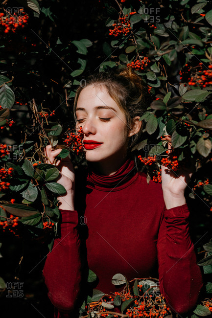 Young female with closed eyes standing amidst green shrub branches with red berries on sunny day in garden